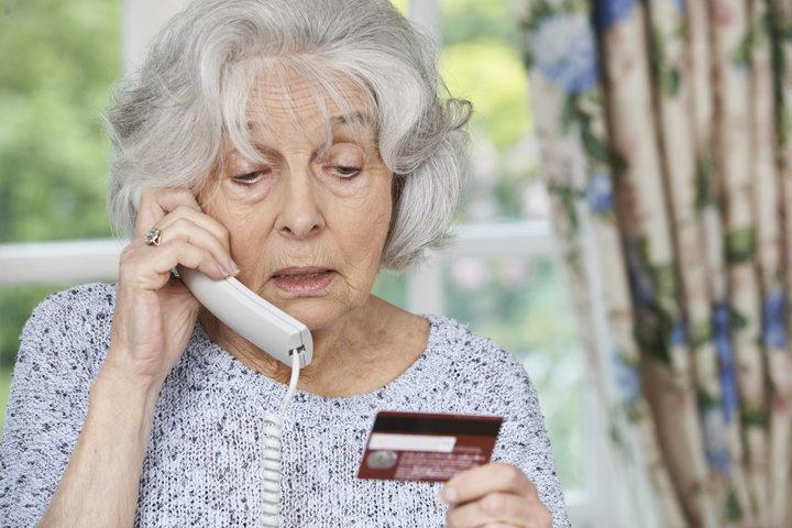 starija zena daje detalje viza kartice preko telefona